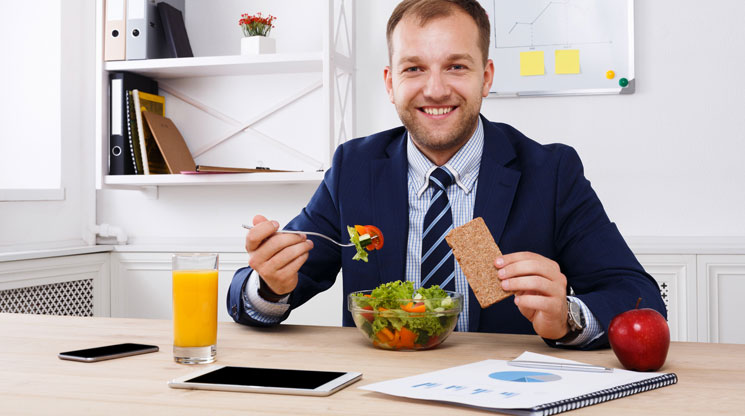 Man eating healthy lunch at work