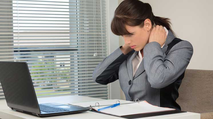 Woman stretching her neck sitting at office furniture