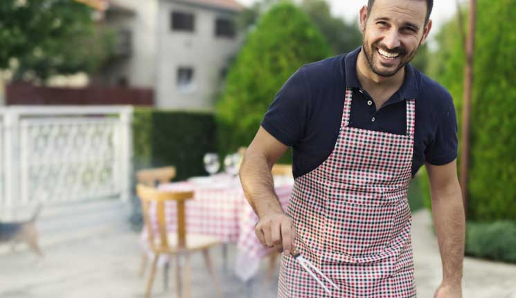 Man in apron grilling